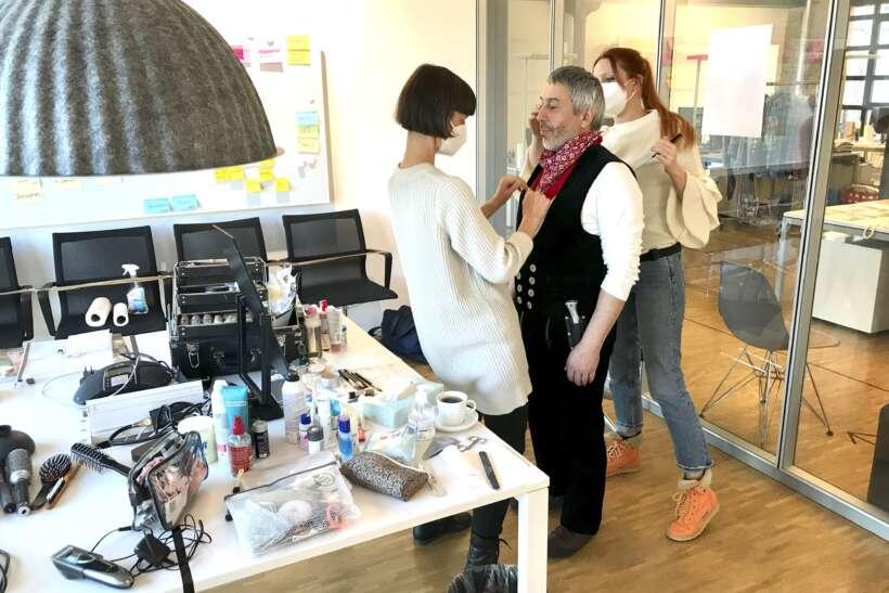 Foto model being prepared by make-up artist